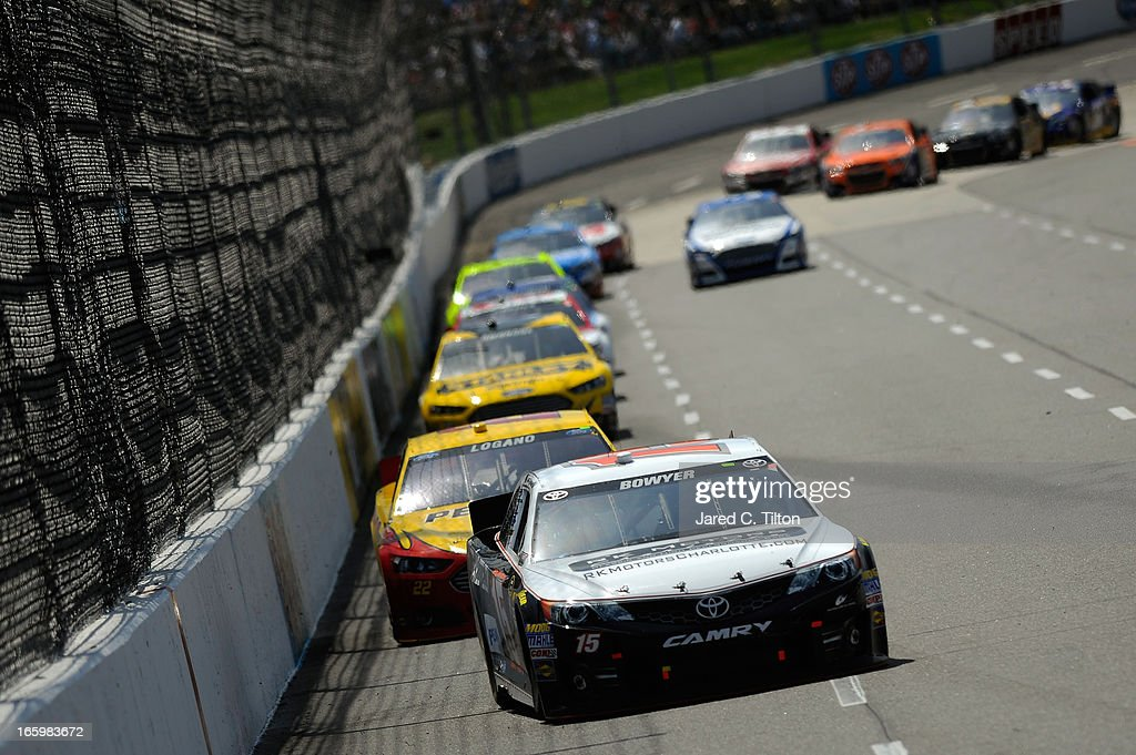 Clint Bowyer, driver of the #15 RK Motors Toyota, leads a group of cars into turn three during the NASCAR Sprint Cup Series STP Gas Booster 500 on April 7, 2013 at Martinsville Speedway in Ridgeway, Virginia.