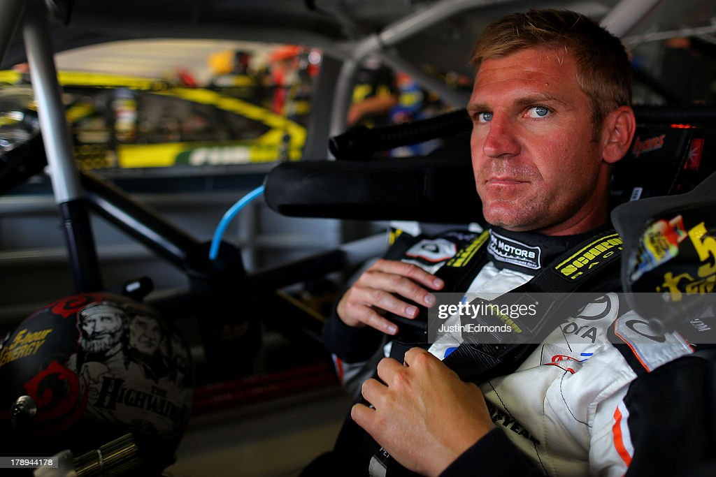 Clint Bowyer, driver of the #15 RKMotorsCharlotte.com Toyota, sits in his car during practice for the NASCAR Sprint Cup Series AdvoCare 500 at Atlanta Motor Speedway on August 31, 2013 in Hampton, Georgia.