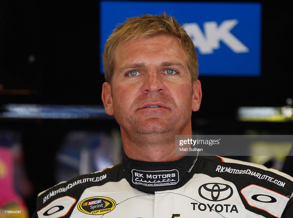 Clint Bowyer, driver of the #15 RKMotorsCharlotte.com Toyota, stands in the garage area during practice for the NASCAR Sprint Cup Series AdvoCare 500 at Atlanta Motor Speedway on August 31, 2013 in Hampton, Georgia.