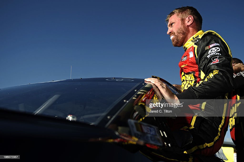 Clint Bowyer, driver of the #15 Sour Apple Extra Strength 5-Hour ENERGY Toyota, climbs from his car after qualifying for the NASCAR Sprint Cup Series AAA Texas 500 at Texas Motor Speedway on November 1, 2013 in Fort Worth, Texas.