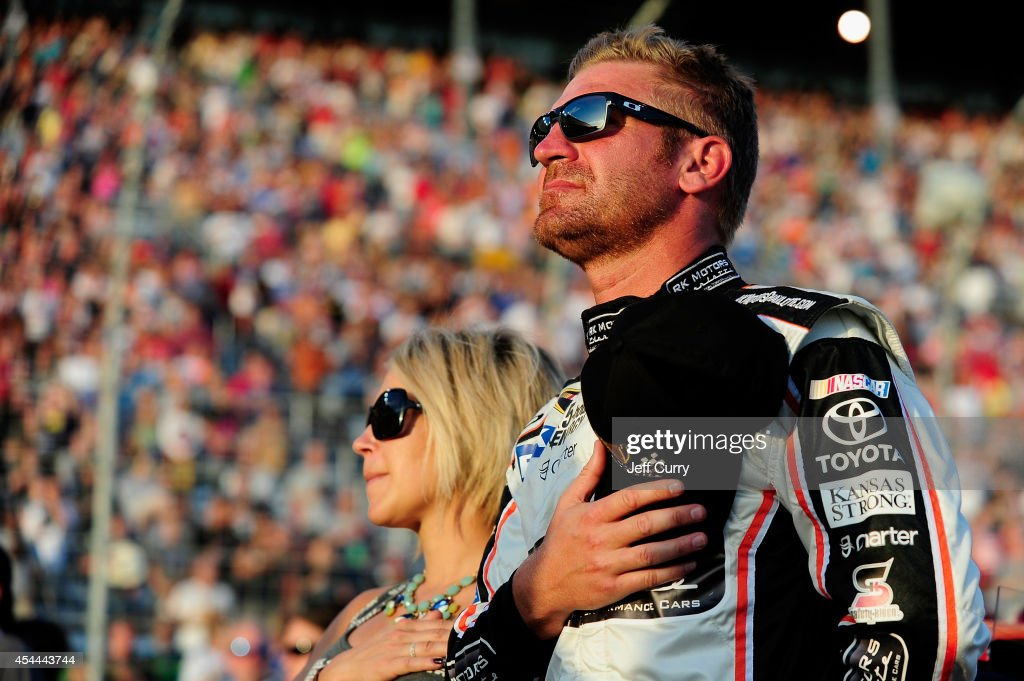 Clint Bowyer, driver of the #15 SpeedDigital.com Toyota, stands on the grid with his wife, Lorra, during the national anthem prior to the NASCAR Sprint Cup Series Oral-B USA 500 at Atlanta Motor Speedway on August 31, 2014 in Hampton, Georgia.