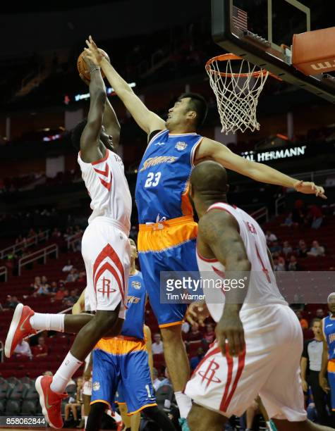Clint Capela of Houston Rockets drives to the basket defended by Zhang Zhaoxu of Shanghai Sharks in the first half at Toyota Center on October 5 2017...
