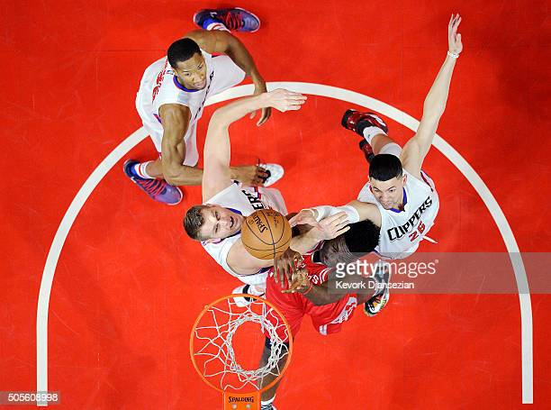 Clint Capela of the Houston Rockets battles for the ball with Cole Aldrich Austin Rivers and Wesley Johnson of the Los Angeles Clippers during the...
