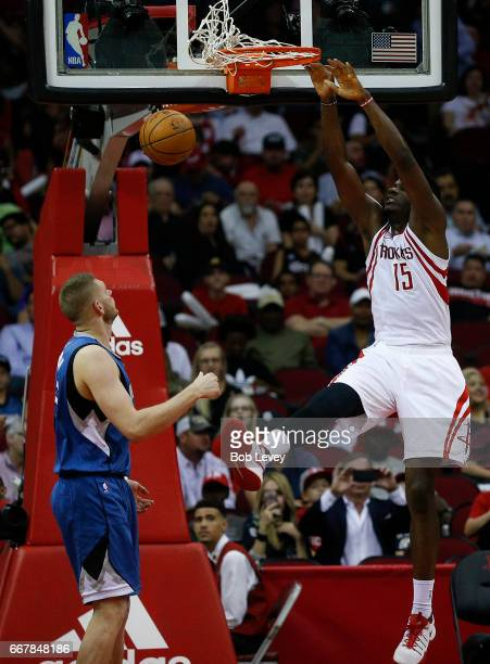 Clint Capela of the Houston Rockets dunks on Cole Aldrich of the Minnesota Timberwolves during the third quarter at Toyota Center on April 12 2017 in...