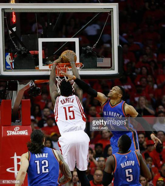 Clint Capela of the Houston Rockets dunks on Russell Westbrook of the Oklahoma City Thunder as Steven Adams and Victor Oladipo during Game Five of...