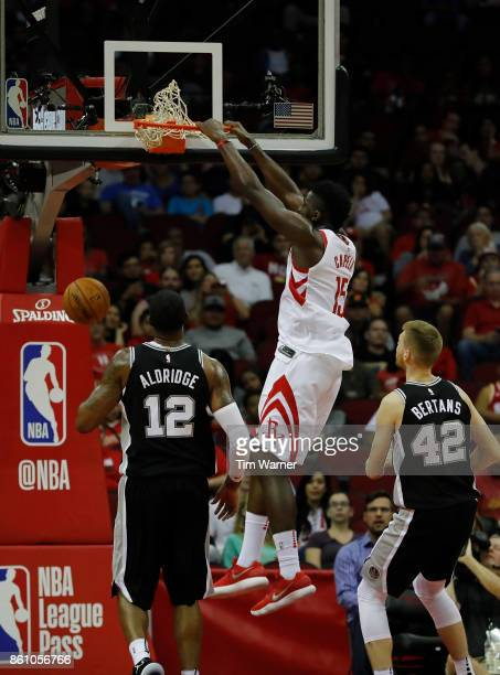 Clint Capela of the Houston Rockets dunks the ball in the first half defended by Davis Bertans of the San Antonio Spurs and LaMarcus Aldridge at...