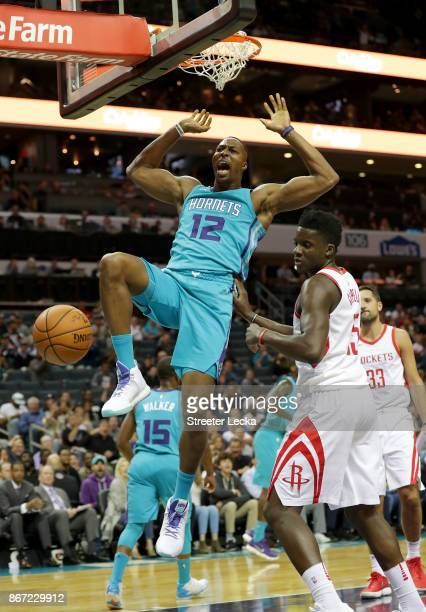 Clint Capela of the Houston Rockets watches as Dwight Howard of the Charlotte Hornets dunks the ball during their game at Spectrum Center on October...