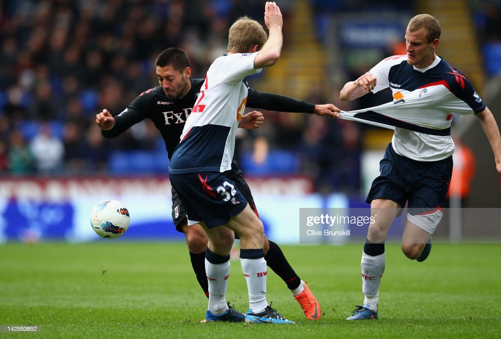 Clint Dempsey of Fulham attempts to move past Tim Ream of Bolton Wanderers during the Barclays Premier League match between Bolton Wanderers and Fulham at Reebok Stadium on April 7, 2012 in Bolton, England.