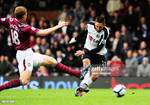 Clint Dempsey of Fulham beats Jonathan Spector of West Ham United to score their first goal during the Barclays Premier League match between Fulham...