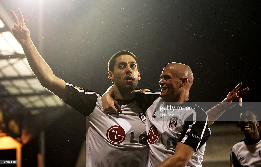 Clint Dempsey of Fulham celebrates scoring with Paul Konchesky during the UEFA Europa League Round of 16 second leg match between Fulham and Juventus...