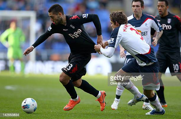 Clint Dempsey of Fulham in action with Marcos Alonso of Bolton Wanderers during the Barclays Premier League match between Bolton Wanderers and Fulham...