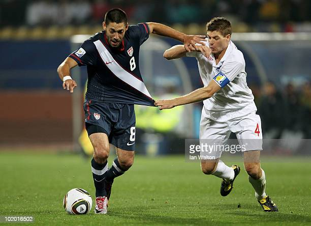 Clint Dempsey of the United States holds off a challenge by Steven Gerrard of England during the 2010 FIFA World Cup South Africa Group C match...