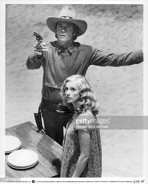 Clint Eastwood aiming gun while Sandra Locke watches in a scene from the film 'Bronco Billy' 1980