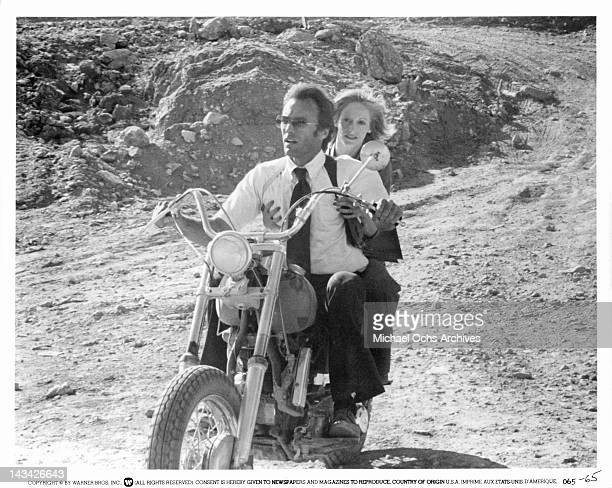 Clint Eastwood and Sondra Locke riding on a motorcycle down a dirt road in a scene from the film 'The Gauntlet' 1977