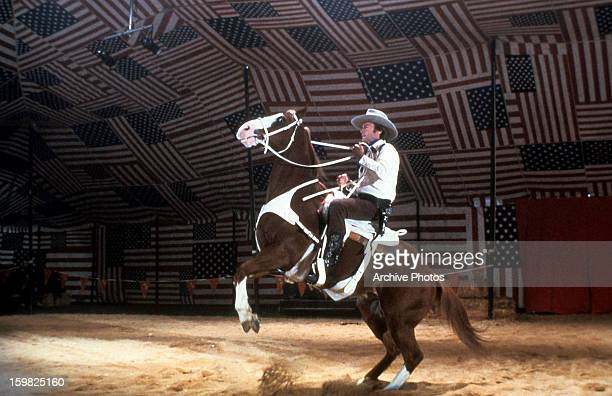 Clint Eastwood holds on as his horse bucks in a scene from the film 'Bronco Billy' 1980