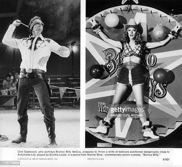 Clint Eastwood prepares to throw a knife at balloons dangerously close to Sandra Locke sitting on the table in a scene from the film 'Bronco Billy'...