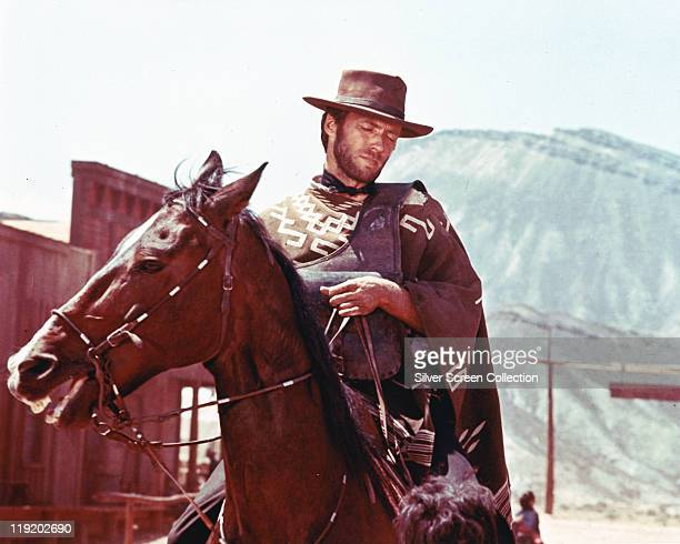 Clint Eastwood US actor and film director wearng a cowboy hat and poncho as he rides a horse playing the 'Man with No Name' character which he played...