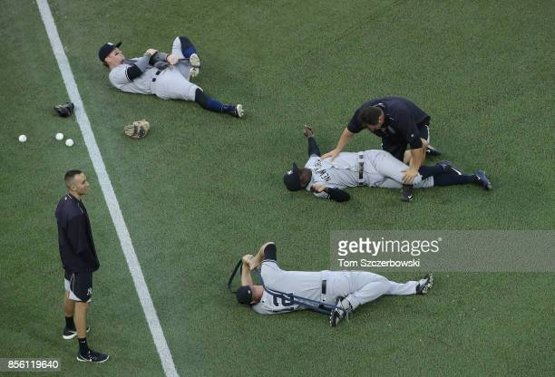 Clint Frazier of the New York Yankees and Didi Gregorius and Chase Headley stretch on the turf as they prepare for their MLB game against the Toronto...
