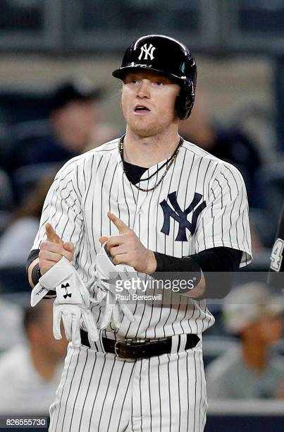 Clint Frazier of the New York Yankees points to his teammates in the dugout after hitting a triple in an MLB baseball game against the Detroit Tigers...