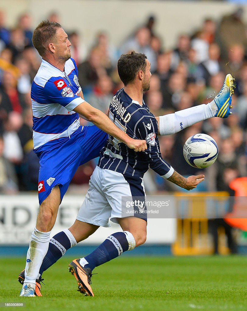 Clint Hill of Queens Park Rangers tackles Scott McDonald of Millwall FC during the Sky Bet Championship match between Millwall and Queens Park...