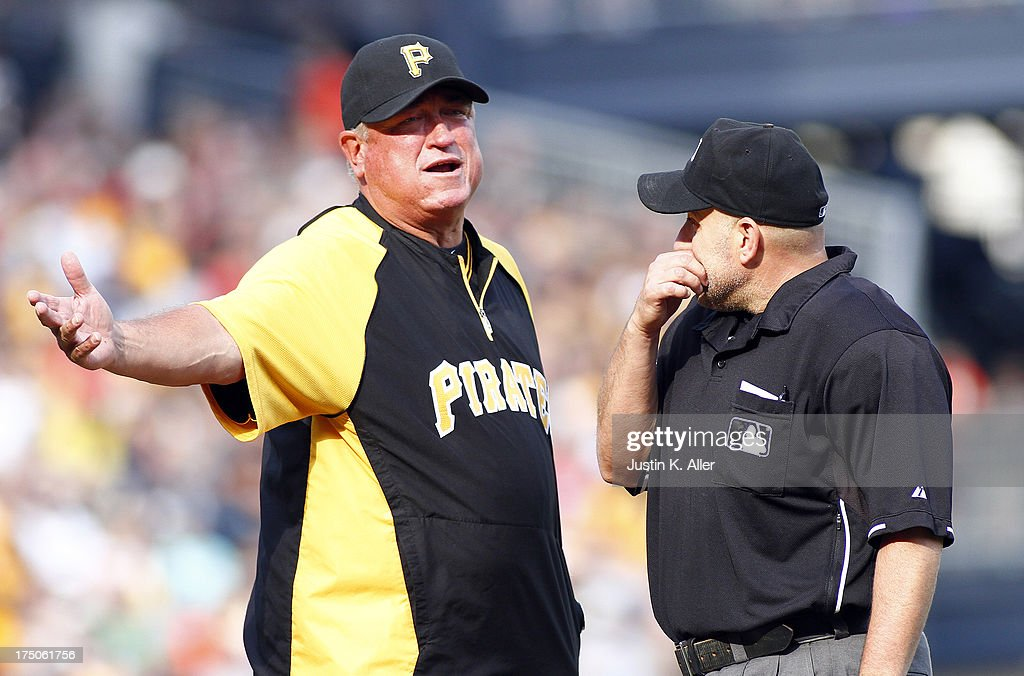 Clint Hurdle #13 of the Pittsburgh Pirates argues a call with home plate umpire Eric Cooper in the sixth inning against the St. Louis Cardinals during the game on July 30, 2013 at PNC Park in Pittsburgh, Pennsylvania. The Pirates defeated the Cardinals 2-1 in eleven innings.