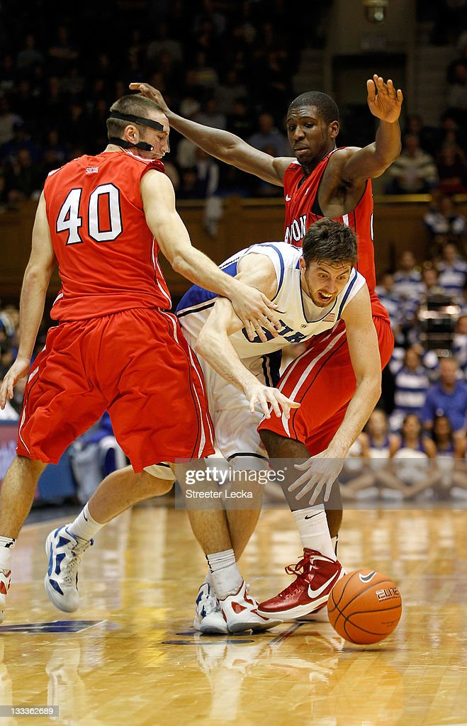 Clint Mann #40 of the Davidson Wildcats and teammate Frank Ben-Eze #34 try to trap Ryan Kelly #34 of the Duke Blue Devils during their game at Cameron Indoor Stadium on November 18, 2011 in Durham, North Carolina.