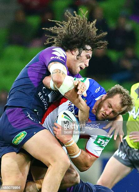 Clint Newton of the Newcastle Knights is tackled by Kevin Proctor of the Melbourne Storm during the round 24 NRL match between the Melbourne Storm...