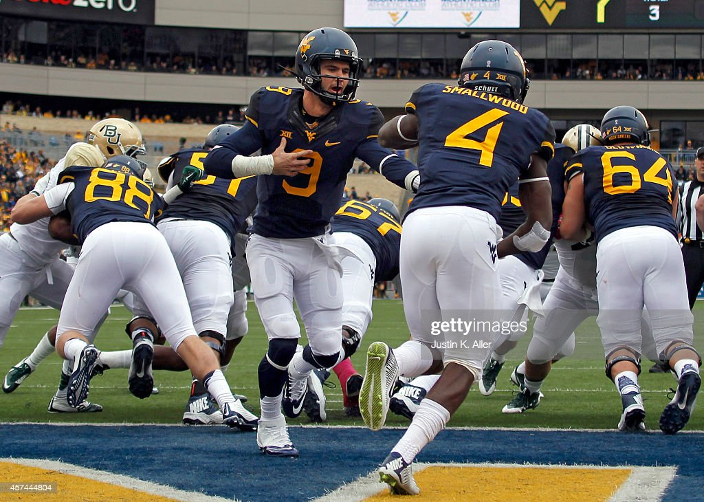 Clint Trickett of the West Virginia Mountaineers hands off to Wendell Smallwood against the Baylor Bears during the game on October 18 2014 at...