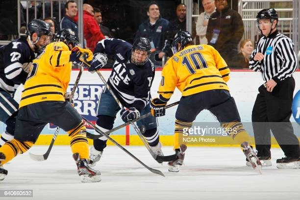 Clinton Bourbonais of Yale makes a second period pass past Connor Jones of Quinnipiac during the Division I Men's Hockey Championship held at the...