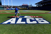 Clinton Elder of the Kansas City Royals grounds crew is seen watering the logo before Game 1 of the ALCS against the Toronto Blue Jays at Kauffman...