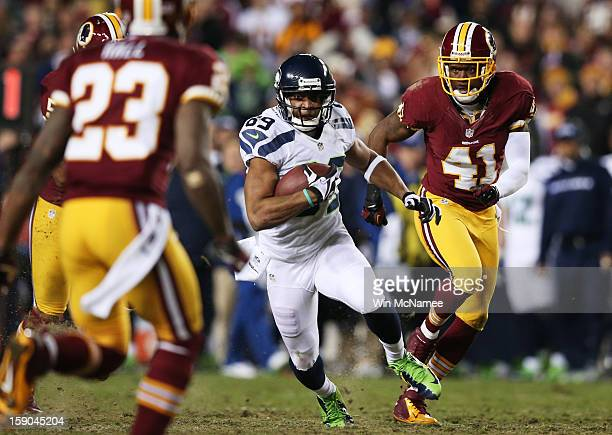 Clinton McDonald of the Seattle Seahawks carries the ball against the defense of Madieu Williams and DeAngelo Hall of the Washington Redskins during...