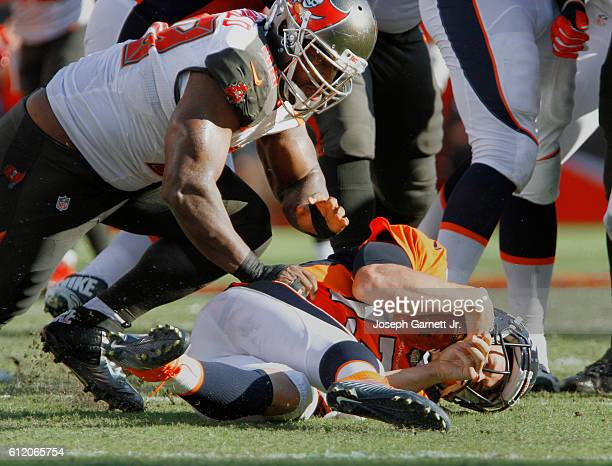 Clinton McDonald of the Tampa Bay Buccaneers slams Trevor Siemian of the Denver Broncos for a sack late in the second quarter during their game at...