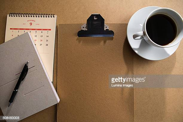 Clipboard and notepad with coffee on table