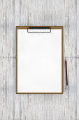 Clipboard, note paper on wooden background with a pen, to do list, checklist