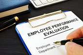 Clipboard with employee performance evaluation and pen.