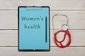 "Medecine concept - clipboard with text ""Women's health"", stethoscope on white wooden background"