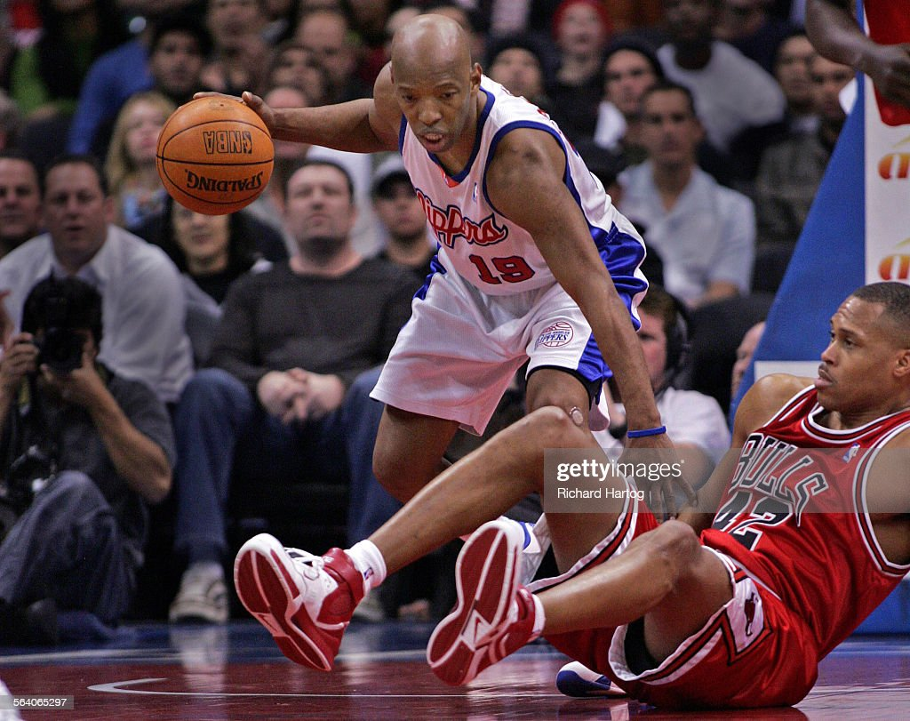 Clipper Sam Cassell left scoops up a loose ball and leaves