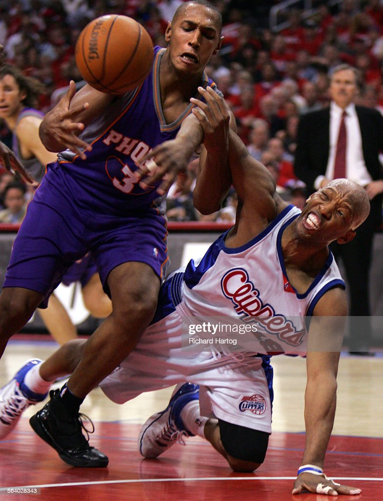 Clipper Sam Cassell right s down to knock the ball away from