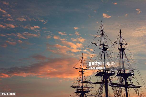 Clipper ship masts in a dramatic evening sky