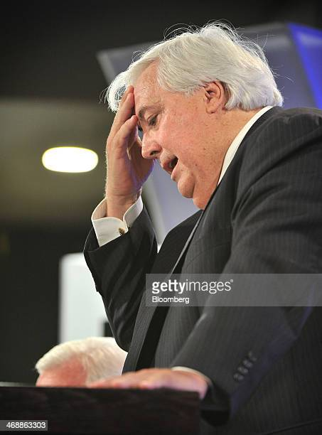 Clive Palmer federal leader of the Palmer United Party and chairman of Mineralogy Pty holds his head as he speaks at the National Press Club in...