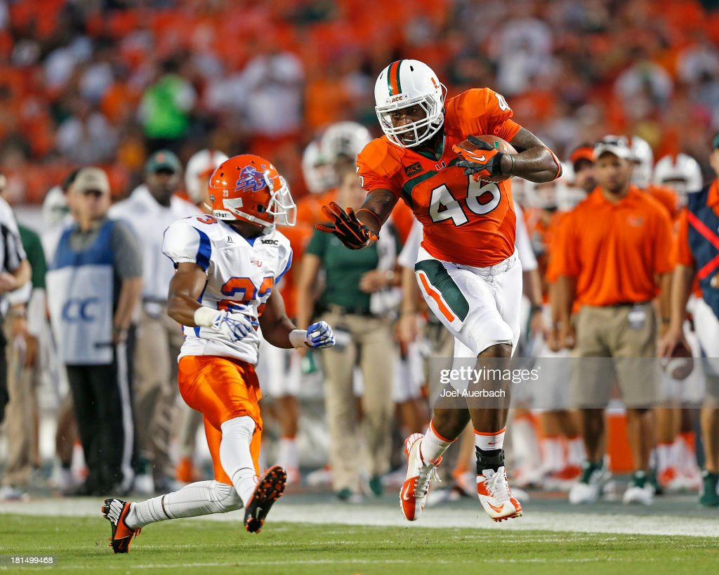 Clive Walford #46 of the Miami Hurricanes runs with the ball while being defended by Romahn Hemingway #23 of the Savannah State Tigers on September 21, 2013 at Sun Life Stadium in Miami Gardens, Florida. Miami defeated Savannah State 77-7.
