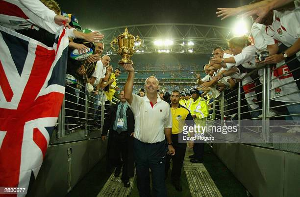 Clive Woodward the coach of England holds aloft the William Webb Ellis trophy as he leaves the field after England's victory in the Rugby World Cup...