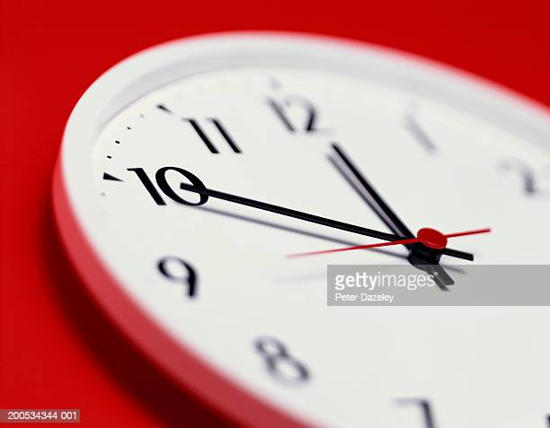 Clock, against red background, close-up, (focus on 10)