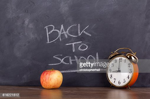 Clock and an apple against a blackboard : Stockfoto