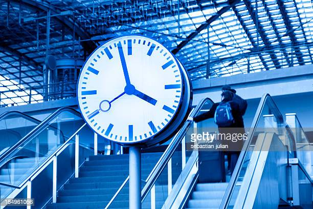 clock and commuters in front of modern railway station ceiling