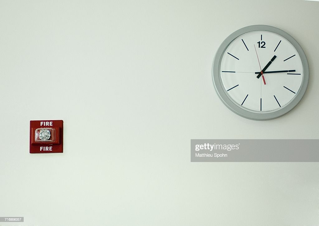 Clock and fire alarm on wall