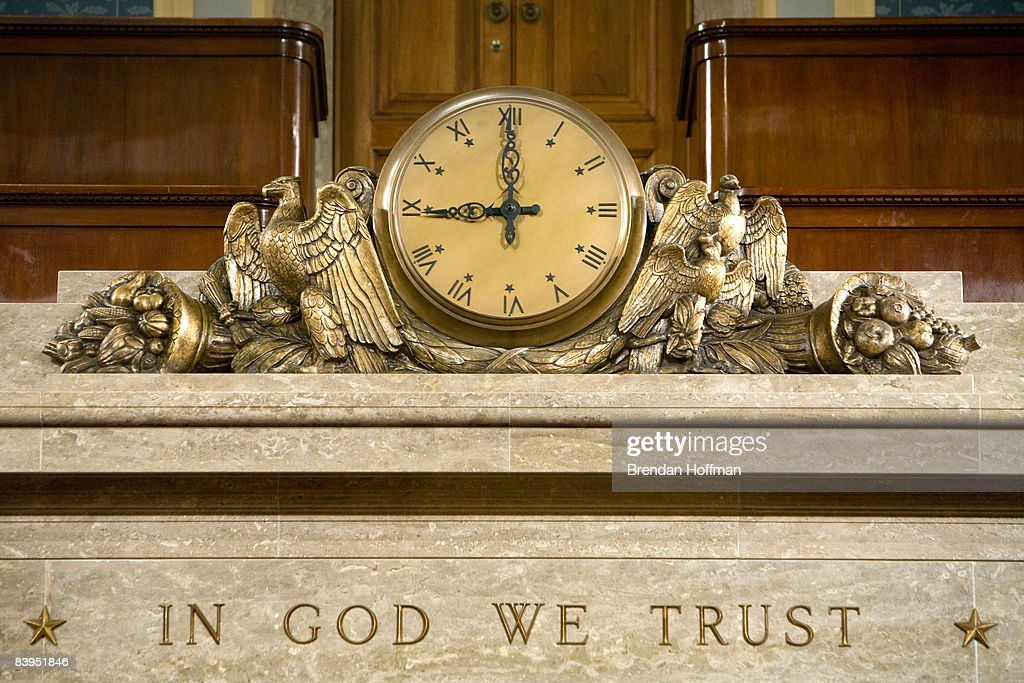 A clock and the motto 'In God We Trust' over the Speaker's rostrum in the US House of Representatives chamber are seen December 8 2008 in Washington...