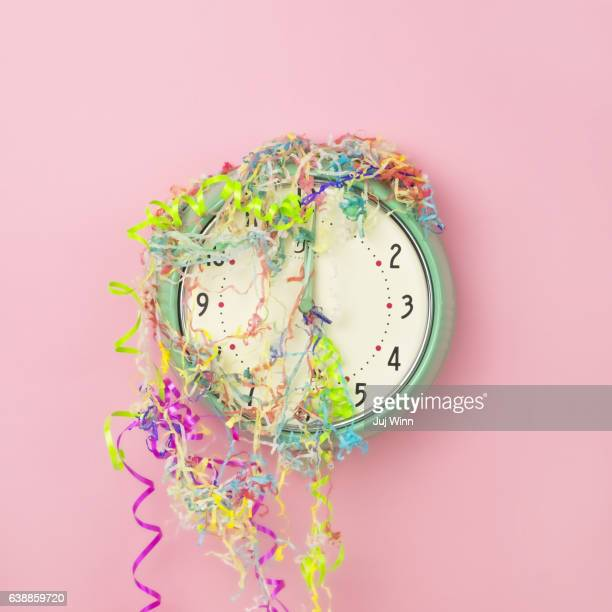 Clock covered in confetti and party streamers