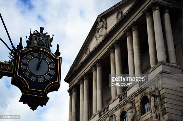 A clock is pictured next to the Bank of England in the City of London on August 19 2014 Britain's 12month inflation slid to 16 percent in July from...