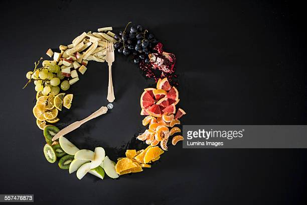 Clock made with fruit, vegetables and flatware